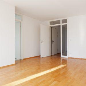 Leere Wohnung mit Dielen und weißen Wänden